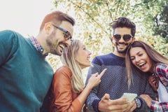 Bild av fyra lyckliga le unga vänner som utomhus går i parkera Arkivbild