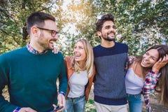 Bild av fyra lyckliga le unga vänner som utomhus går i parkera Royaltyfria Bilder