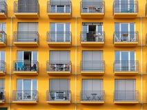 Bild av gul hög löneförhöjningbyggnad med fönster och balkonger och rullgardiner arkivfoton