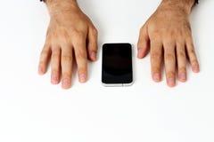 Bild av händer för en man på en vit tabell Arkivfoto