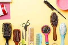 Bild av hårkammar och sax som isoleras på gul bakgrund Arkivfoto