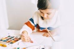 Bild av konstnärlig liten flickamålning med oljablyertspennor som hemma sitter på det vita skrivbordet Nätt le förskole- ungeteck royaltyfri foto