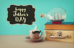 Bild av koppen kaffe, den gamla boken, den gamla resväskaasken och fartyget i flaskan över trätabellen Begrepp för dag för fader` Royaltyfri Bild