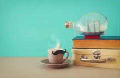 Bild av koppen kaffe, den gamla boken, den gamla resväskaasken och fartyget i flaskan över trätabellen Begrepp för dag för fader` Royaltyfri Fotografi