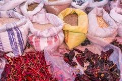 Bild av korn i säckar och röda torra chilipeppar och pasillachili i en mexikansk marknad royaltyfri fotografi