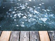 Bild av krossad is på djupfrysta sjö- och träplankor arkivbilder