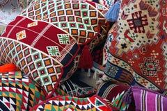 Bild av kulöra orientaliska kuddar och textilen med traditionell design arkivbild