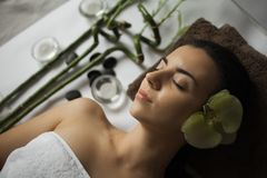 Bild av kvinnan i brunnsortsalongen som ligger på massageskrivbordet royaltyfri foto