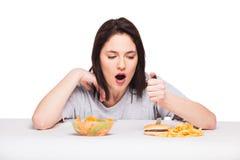 Bild av kvinnan med frukter och hamburgaren framme på vitbac arkivbild