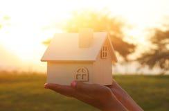 Bild av kvinnan som utomhus rymmer det lilla trähuset på solnedgångljus royaltyfri foto