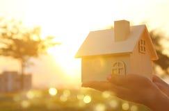 Bild av kvinnan som utomhus rymmer det lilla trähuset på solnedgångljus royaltyfria foton