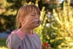 Bild av lilla flickan som blåser luftbubblor med sikt av gröna träd och filialer bakom arkivbild
