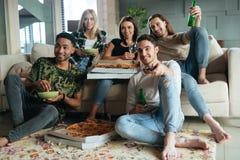 Bild av lyckliga fem vänner som håller ögonen på TV Royaltyfri Foto