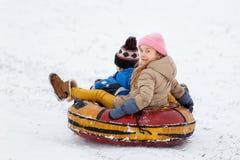 Bild av lyckliga flicka- och pojkeridningrör Arkivbild