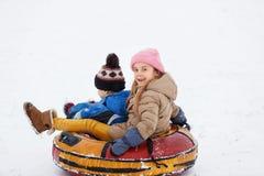 Bild av lyckliga flicka- och pojkeridningrör Arkivbilder