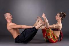 Bild av mannen och kvinnan som tillsammans gör yoga Arkivbild