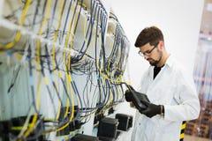 Bild av modem för nätverksteknikerprovning i fabrik royaltyfria foton