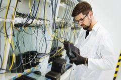 Bild av modem för nätverksteknikerprovning i fabrik royaltyfri bild