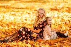 Bild av modern och dottern som sitter på sidor i höst royaltyfria bilder