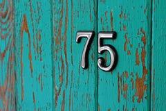 Bild av nummer 75 på den träsjaskiga väggen Royaltyfri Bild