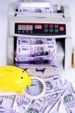 Bild av ny indisk valuta, kassa som räknar maskinen, förstoringsglas och gul spargris royaltyfria foton