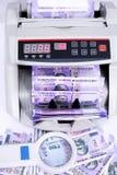 Bild av ny indisk valuta, kassa som räknar maskinen och förstoringsglaset arkivfoton
