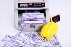 Bild av ny indisk valuta, kassa som räknar maskinen och spargrisen fotografering för bildbyråer