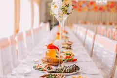 Bild av orange färg för tabellinbrott på en lyxig bröllopkorridor, närbild royaltyfri foto
