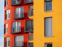Bild av röda två och gula höga löneförhöjningbyggnader med fönster och balkonger och rullgardiner arkivbilder