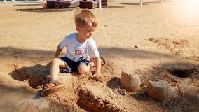 Bild av 3 ?r gammal liten litet barnpojke som sitter p? havsstranden och den byggande slotten fr?n v?t sand fotografering för bildbyråer