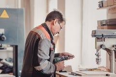 Bild av snickaren som använder den elektriska drillborren royaltyfri bild