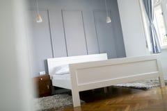 Bild av sovrummet i mjuka ljusa färger och bekväm säng royaltyfria foton