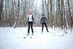 Bild av sportar kvinna och manskidåkning i vinterskog Arkivfoto