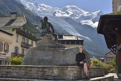 Bild av stadsfyrkanten med statyn och en handelsresande Mont Blanc i bakgrund Royaltyfri Foto
