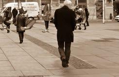 Bild av stadsgångarefyrkanten med mannen som förbi strosar Duvor som flyger ovanför folkhuvud Sepiasignalbild Europa 01 02 2018 Arkivfoto