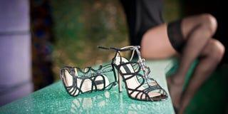 Bild av svarta skor på smaragdyttersida i förgrunds- och kvinnalår på bakgrund Arkivbilder