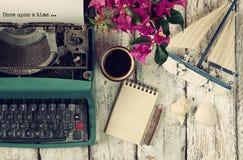 Bild av tappningskrivmaskinen med uttryck en gång på en tid, en tom anteckningsbok, en kopp kaffe och en gammal segelbåt arkivfoton