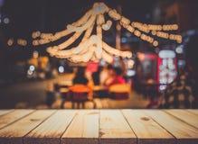 Bild av trätabellen framme av abstrakt suddig restaurangli Royaltyfria Foton