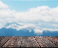 Bild av trätabellen framme av abstrakt suddig bakgrund av berget användas för skärm eller montage kan dina produkter åtlöje arkivfoton