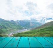 Bild av trätabellen framme av abstrakt suddig bakgrund av berget användas för skärm eller montage kan dina produkter åtlöje royaltyfri bild