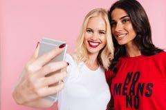 Bild av två nätta lyckliga kvinnor som gör selfie på smartphonen Arkivfoton