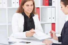 Bild av undertecknande avtalspapper för två kvinna Arkivbilder