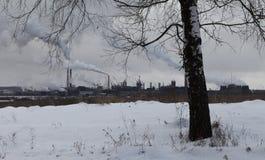 Bild av vinterlandskapet med industrianläggningen Arkivbilder