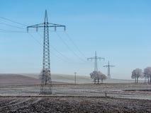 Bild av vinterlandskapet med kraftledningar fotografering för bildbyråer