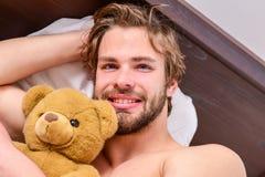 Bild, das den jungen Mann ausdehnt im Bett zeigt Bemannen Sie glaubenden hinteren Schmerz im Bett, nachdem Sie geschlafen haben M lizenzfreie stockfotografie