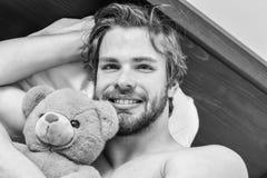 Bild, das den jungen Mann ausdehnt im Bett zeigt Bemannen Sie glaubenden hinteren Schmerz im Bett, nachdem Sie geschlafen haben M stockfotos
