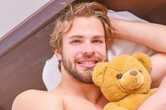 Bild, das den jungen Mann ausdehnt im Bett zeigt Bemannen Sie glaubenden hinteren Schmerz im Bett, nachdem Sie geschlafen haben M lizenzfreies stockbild