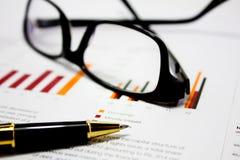 Geschäftsdiagramme mit Gläsern und Stift Stockbild