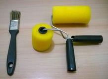 Bild der Bürste und der Minifarbenrolle kreuzte in der grundlegenden Farbe Stockfoto