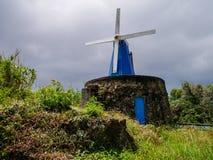 Bild der blauen hölzernen Windmühle auf einer Steinbasis stockfotografie